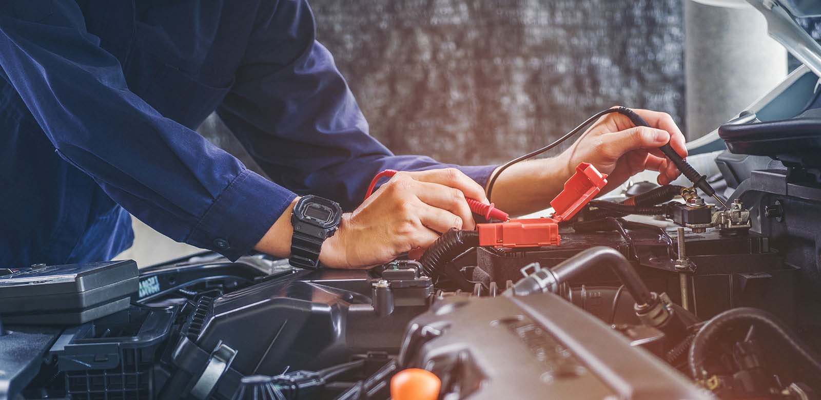 Auto mechanic working on car battery